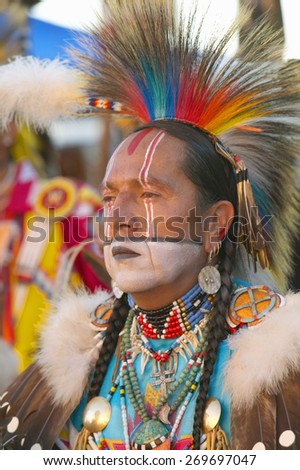 Close-up portrait of Native American in full regalia dancing at Pow wow - stock photo
