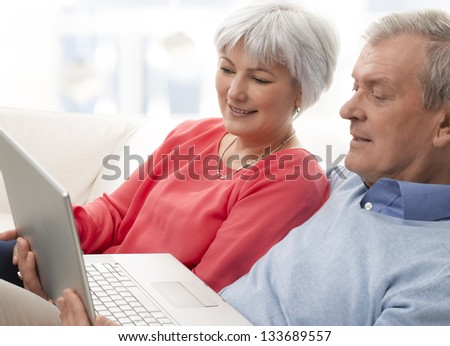Close-up portrait of of a senior couple sitting on the couch, smiling and using laptop in the living room - stock photo