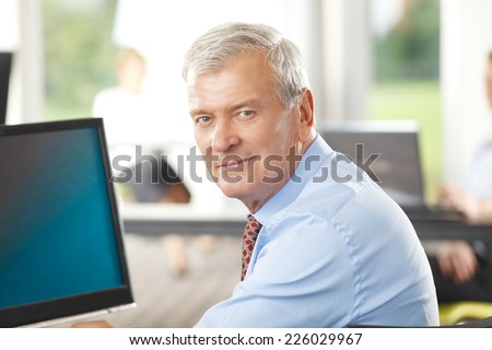 Close-up portrait of old businessman sitting at office.  - stock photo