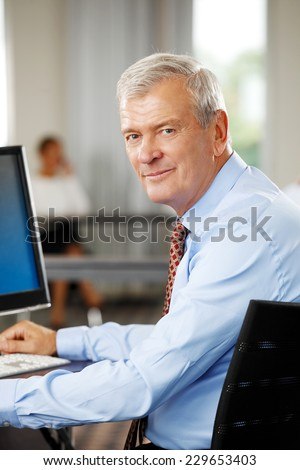 Close-up portrait of old businessman sitting at office while using computer. Business people. - stock photo