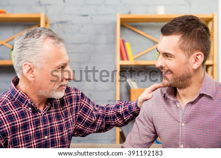 Close up portrait of old father and his happy son laughing - stock photo