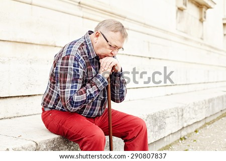 Close-up portrait of pensive mature man in glasses and plaid shirt resting leaning on his wooden walking stick - stock photo