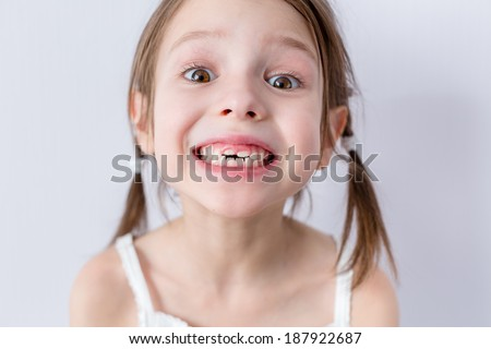 Close up portrait of preschooler girl with open mouth without milk tooth - stock photo