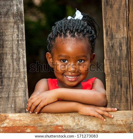 Close up portrait of pretty african youngster leaning on wooden fence outdoors. - stock photo
