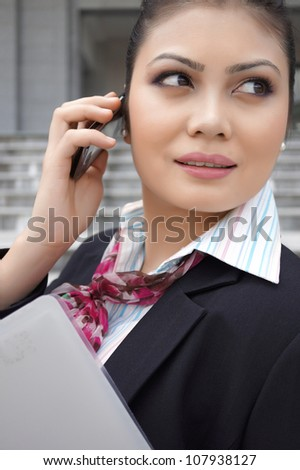 Close-up portrait of pretty Asian lady using mobile phone - stock photo