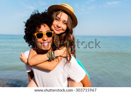 Close up portrait of pretty couple in love  having fun on beach holidays together. Stylish hipster lovers posing on  amazing  beach blue ocean background.  - stock photo
