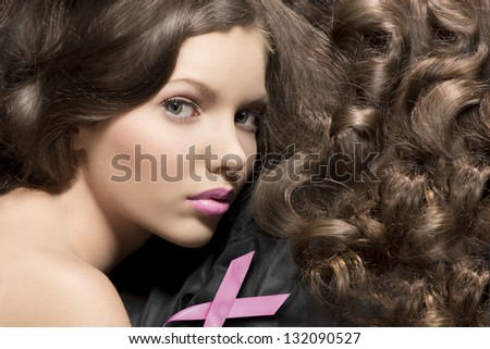 close-up portrait of pretty girl with gloss wavy hair on black material and a pink bow near face - stock photo