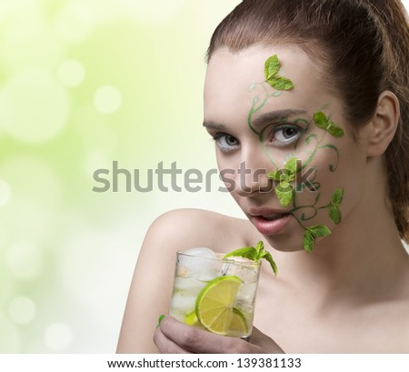 close-up portrait of pretty girl with green creative make-up and some mint leaves on the face, drinking mojito - stock photo