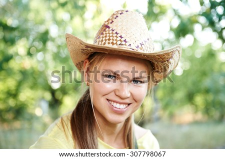 Close-up portrait of pretty smiling woman farmer wearing straw hat on nature. Female winegrower posing in the garden.   - stock photo
