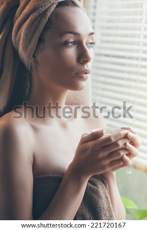 close up portrait of pretty woman drinking coffee in bathrobe - stock photo