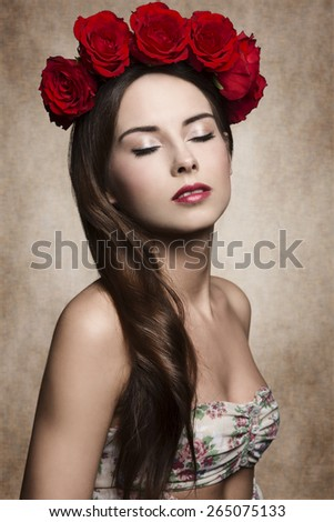 close-up portrait of pretty woman with long smooth brown hair, relaxed expression  and sprig dress posing with red roses on the head and natural make-up  - stock photo