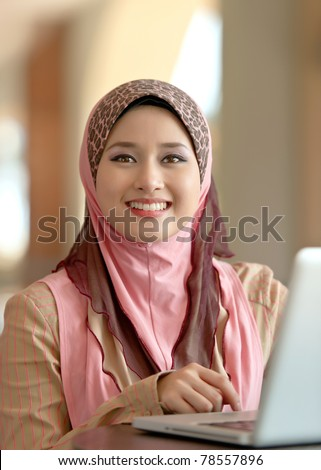 Close-up portrait of pretty young Asian Muslim woman at coffee shop while surfing internet - stock photo