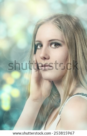 Close up Portrait of Pretty Young Blond Woman with her hand to her face While Looking at the Camera on Abstract Glowing Background. - stock photo