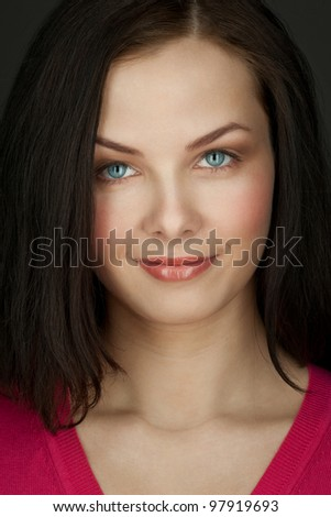 Close-up portrait of pretty young woman looking at camera - stock photo