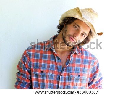 Close up portrait of rugged young man with plaid shirt and cowboy hat - stock photo