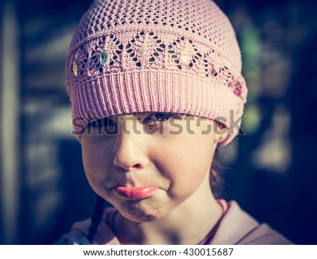 Close-up portrait of sad little girl with pursed lips. - stock photo