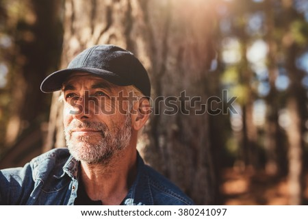 Close up portrait of senior man wearing cap looking away. Mature man with beard sitting in woods on a summer day. - stock photo