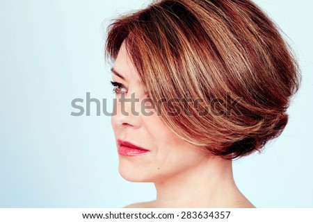 Close up portrait of sensual mature woman with elegant short haircut and natural makeup on blue background - stock photo