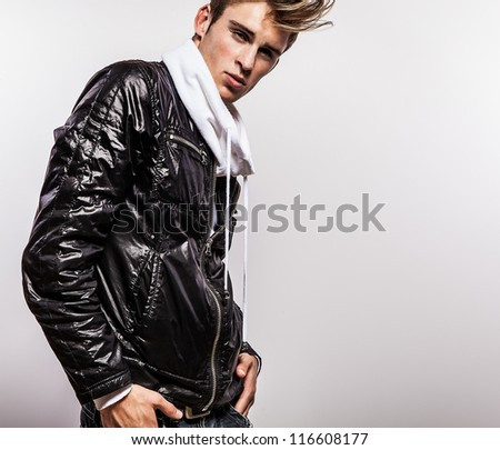 Close-up portrait of sensual young model man on black autumn jacket. - stock photo