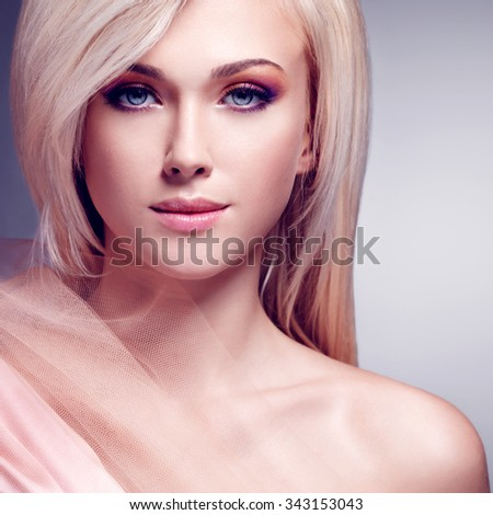 Close-up portrait of sensual young woman in the beige silk over gray background. - stock photo
