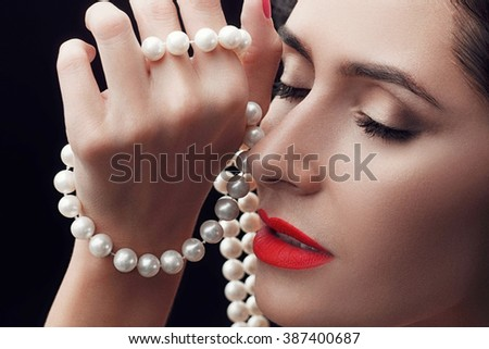 Close-up portrait of sensuality beautiful woman face with a string of pearls, fashion make-up, sexy evening red lips  - stock photo