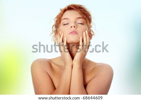 Close-up portrait of sexy caucasian young redhead woman touching her face - stock photo