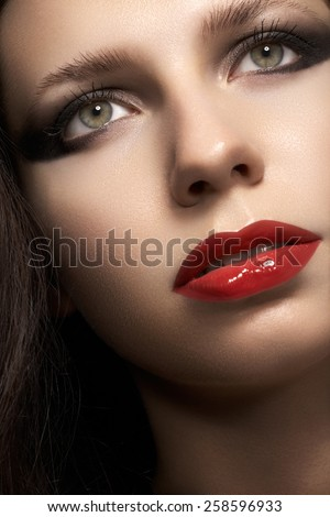 Close-up portrait of sexy caucasian young woman model with glamour red lips make-up, eye arrow makeup, purity complexion. Perfect clean skin. Retro beauty style. - stock photo