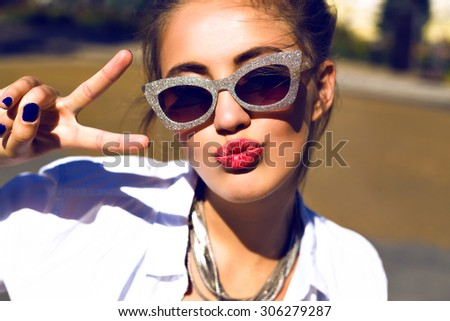 Close up portrait of sexy hipster girl sending kiss and showing cool science by her hands, bright make up, extravagant sunglasses, warm toned colors. making selfie, having fun. - stock photo