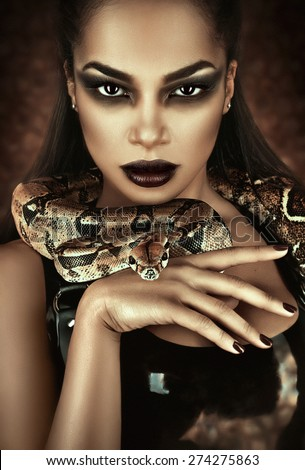 Close up portrait of sexy woman with snake in latex outfit - stock photo