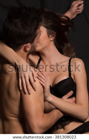 Close-up portrait of sexy young couple body at night: kissing, holding hands. Romantic atmosphere over dark background. - stock photo
