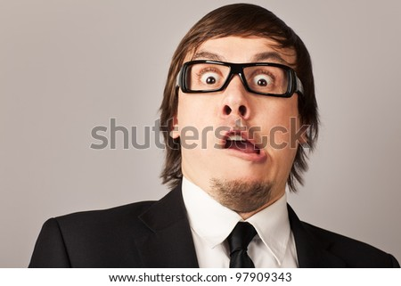 Close-up portrait of shocked businessman, hearing some news. On a gray background - stock photo