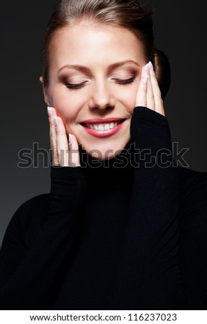 close up portrait of smiley and alluring female against dark background - stock photo