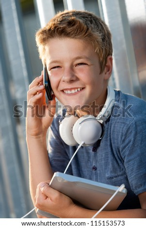 Close up portrait of smiling boy talking on smart phone outdoors. - stock photo