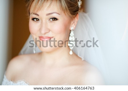Close up portrait of smiling bride on orange background with veil and earrings in wedding dress. - stock photo