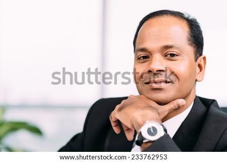Close-up portrait of smiling confident businessman - stock photo