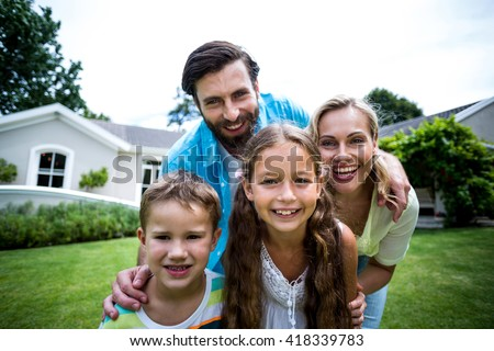 Close-up portrait of smiling family standing outside house in yard - stock photo
