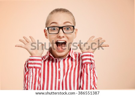Close-up portrait of surprised beautiful girl holding her head in amazement and open-mouthed. Over color background. - stock photo