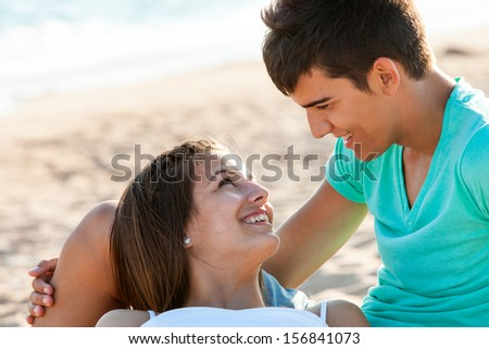 Close up portrait of teen couple sharing romantic moment on beach. - stock photo