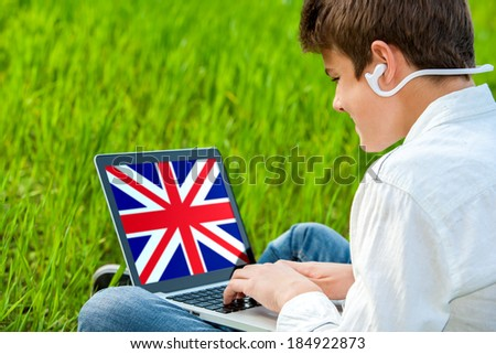 Close up portrait of teen student learning English on laptop. - stock photo