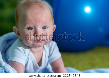Close-up portrait of the baby. Blue ball on background. - stock photo