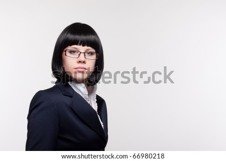 Close up  portrait of the beautiful young woman in a business suit and glasses on a light background - stock photo