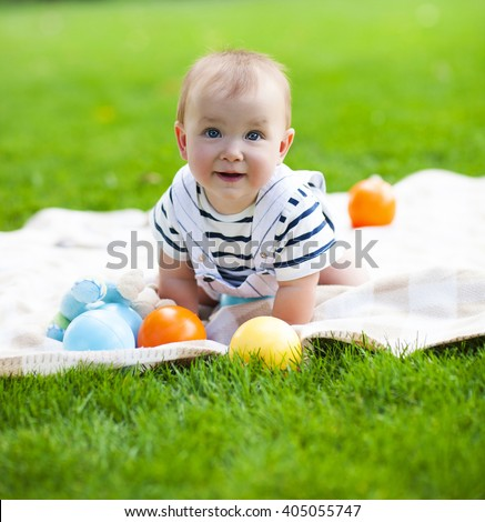 Close up portrait of the smiling baby boy playing outdoors - stock photo