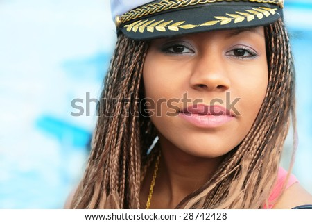 close-up portrait of the smiling girls with braids and in cap on the blue background - stock photo