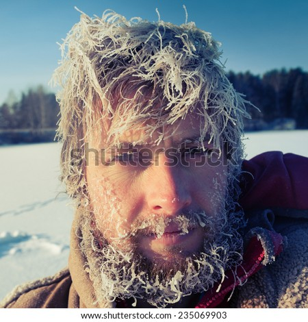 Close up portrait of the young man with frozen icy hairs on head and beard - stock photo