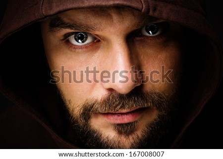 Close-up portrait of threatening man with beard wearing a hood  - stock photo