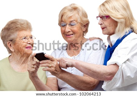 Close up portrait of three happy elderly women with cellphone.Isolated on white. - stock photo