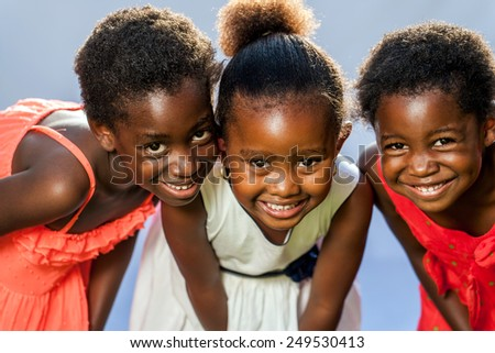 Close up portrait of three small happy African girls with heads together. - stock photo