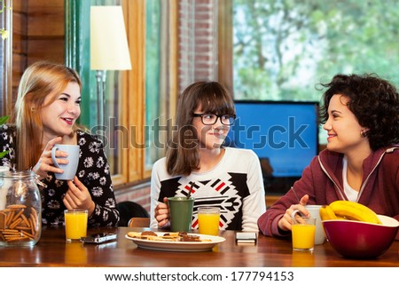 Close up portrait of three young girls having conversation over breakfast at home.  - stock photo