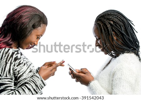 Close up portrait of two attractive african teen girls typing on smart phones. Side view of girls isolated on white background. - stock photo