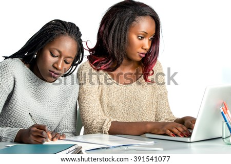 Close up portrait of two female african teen students working doing homework together.Girl with braids hair writing with pen in notebook and another girl typing on laptop.Isolated on white background. - stock photo